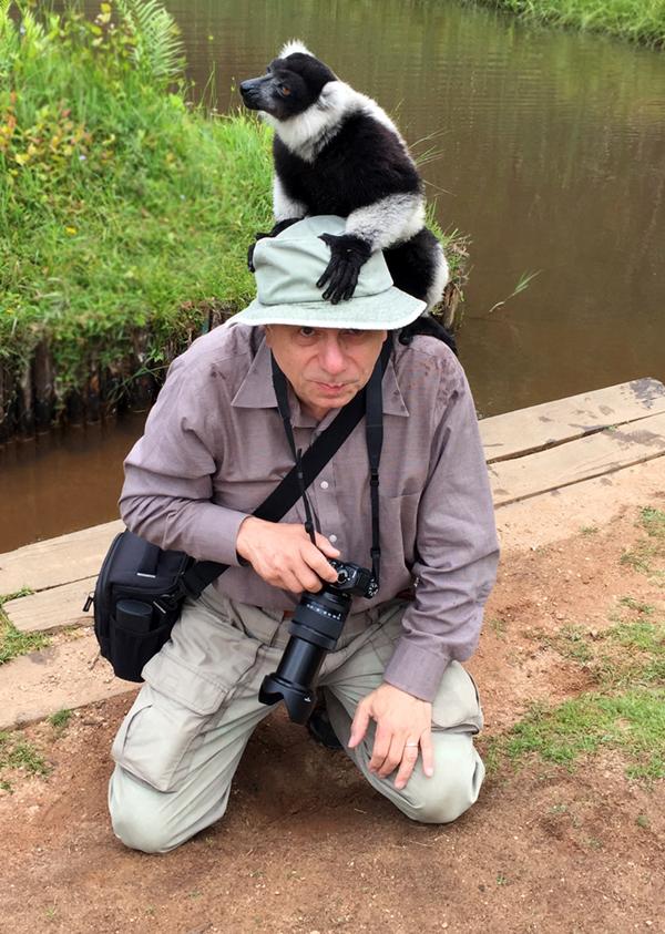 Alex Shaland holding his camera with a Lemur sitting on Alex's head.